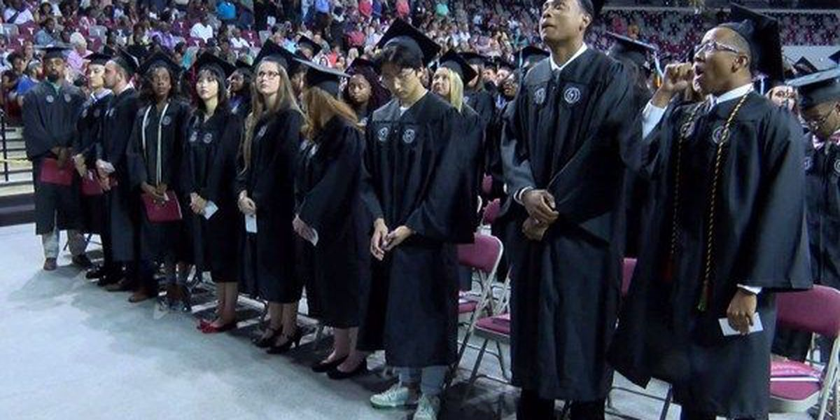Graduates walk across the stage at Troy summer commencement