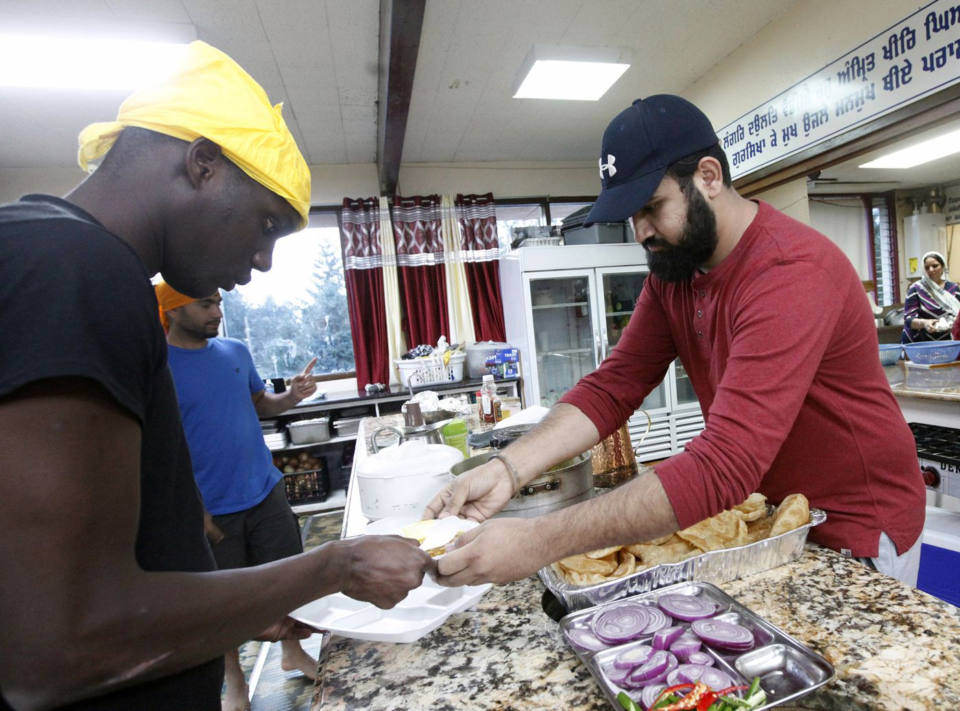 In this Wednesday, Oct. 3, 2018, photo, Karandeep Singh, right, serves a bowl of curry to Abdoulaye Camara at the Dasmesh Darbar Sikh temple in Salem, Ore. Both are immigrants who were recently freed from the federal prison in Sheridan, Ore. Singh was released in late August 2018, and Camara had been released that afternoon. (AP Photo/Amanda Loman)