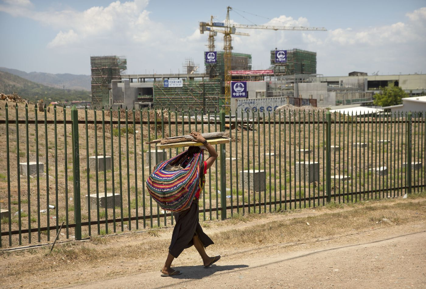 In this Nov. 14, 2018, photo, a woman carrying a bundle of sticks on her head walks past a building being built by Chinese state-owned construction firm China Railway Group Limited in Port Moresby, Papua New Guinea. As world leaders arrive in Papua New Guinea for a Pacific Rim summit, the welcome mat is especially big for China's president. With both actions and words, Xi Jinping has a compelling message for the South Pacific's fragile island states, long both propped up and pushed around by U.S. ally Australia: they now have a choice of benefactors. (AP Photo/Mark Schiefelbein)
