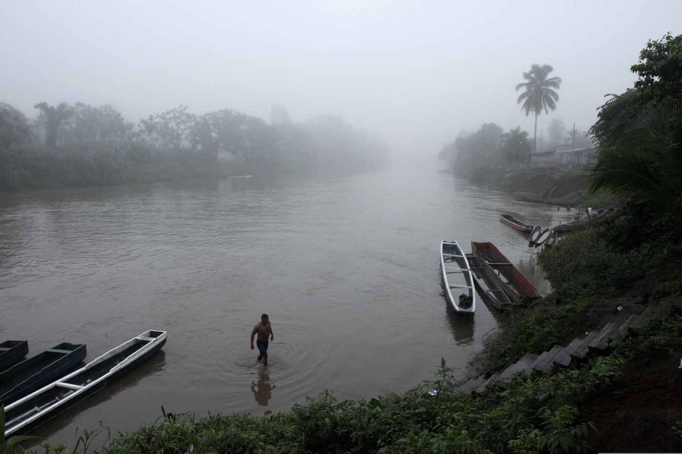 FILE - In this June 22, 2012, file photo, a man bathes in a river at dawn in the Darien Province on the border with Colombia, in Union Choco, Panama. The area is known as the Darien Gap, a 60-mile (97-kilometer) stretch of roadless jungle straddling the border of Colombia and Panama. One man's journey to America from his home in Mauritania was a dangerous and arduous one that took him through the Darien Gap. (AP Photo/Arnulfo Franco, File)
