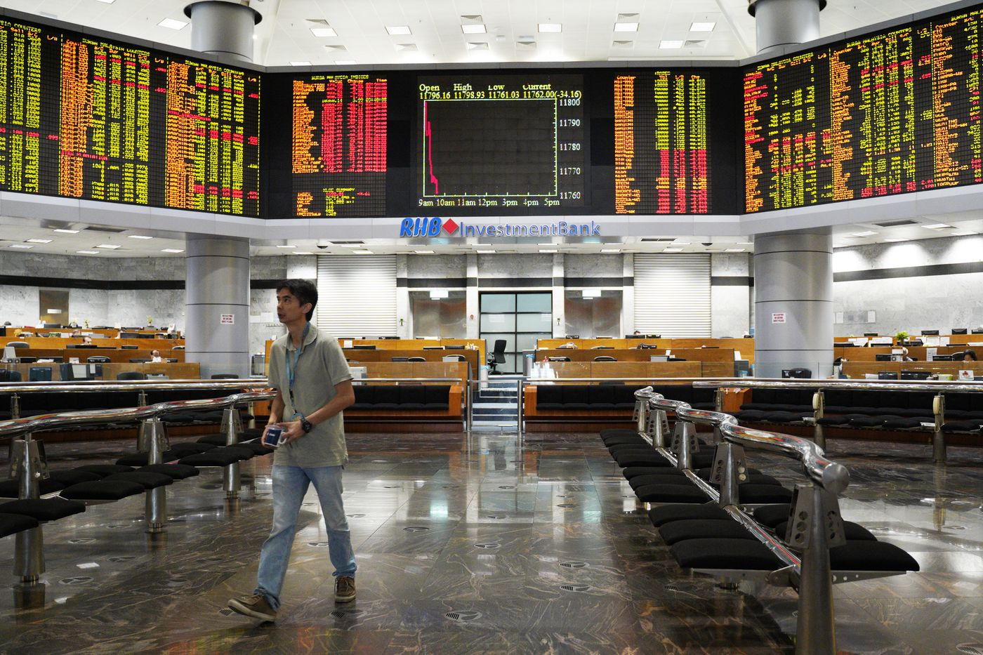 An Investor walks in front of private stock trading boards at a private stock  market gallery